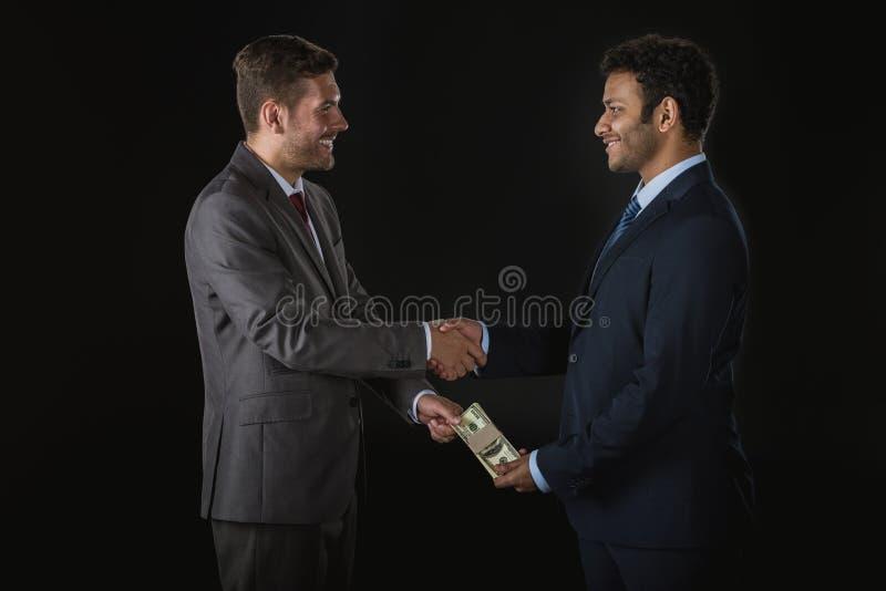 Affärsman som ger pengar och muter affärspartnern som isoleras på svart royaltyfri fotografi