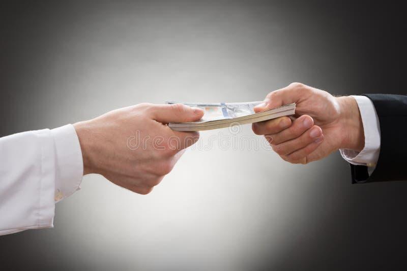Affärsman som ger pengar till doktorn arkivbild