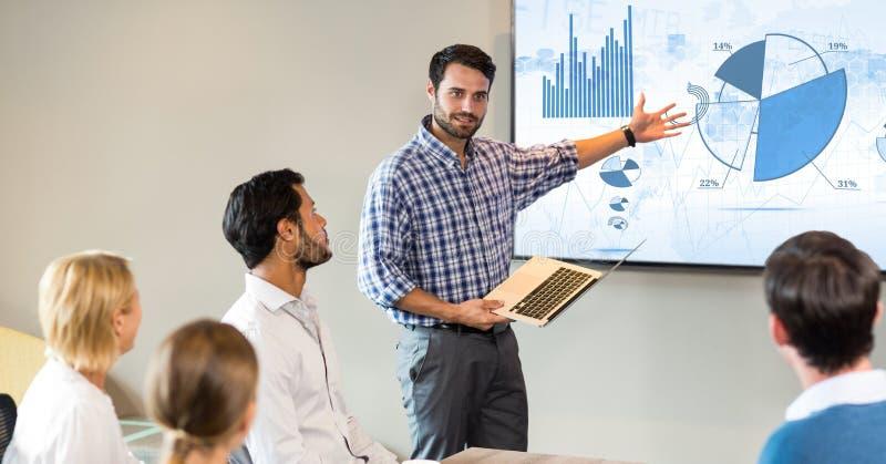 Affärsman som ger presentation till hans kollegor arkivfoto