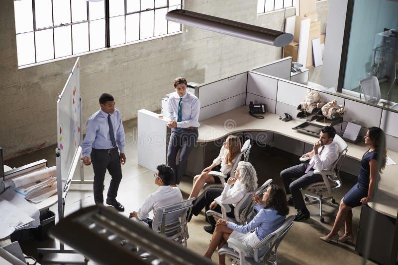 Affärsman som ger presentationen till kollegor, höjd sikt arkivfoto