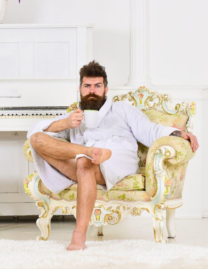 Affärsman som har frukosten i dyrt hotell Grabbsammanträde i antik fåtölj i vitt rum Avkopplad man som tycker om arkivbilder