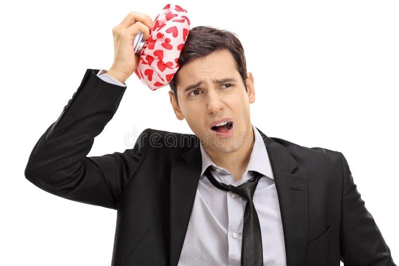 Affärsman som har huvudvärk, och innehav en icepack royaltyfria foton