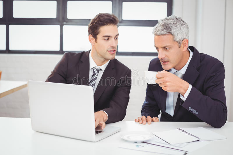 Affärsman som har kaffe, medan arbeta med kollegan arkivfoton