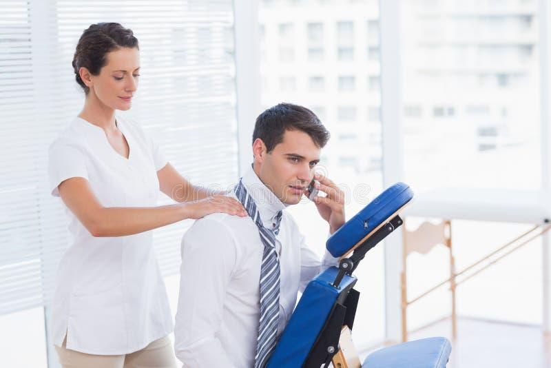 Affärsman som har tillbaka massage, medan tala på telefonen fotografering för bildbyråer