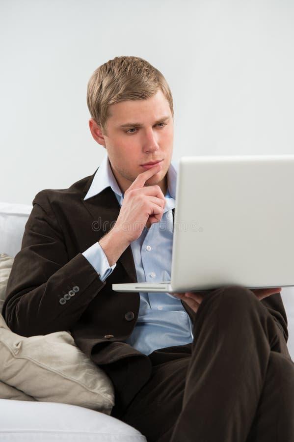 Affärsman som hemma arbetar med bärbara datorn arkivbild