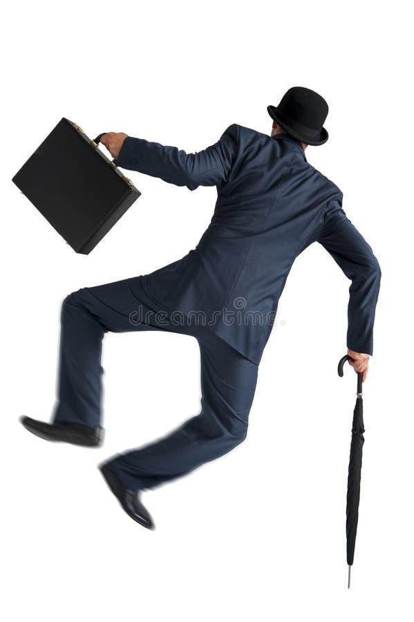 Affärsman som hoppar och sparkar hans häl som isoleras på vit arkivbild