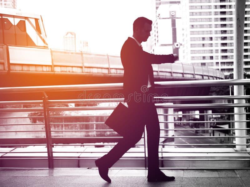 Affärsman som i all hast går på skywalken I hans hand är en svart piskar portföljen Med signalljusljus arkivbilder