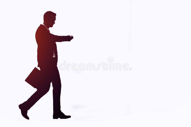 Affärsman som i all hast går på skywalken I hans hand är en svart piskar portföljen Med signalljusljus royaltyfria bilder
