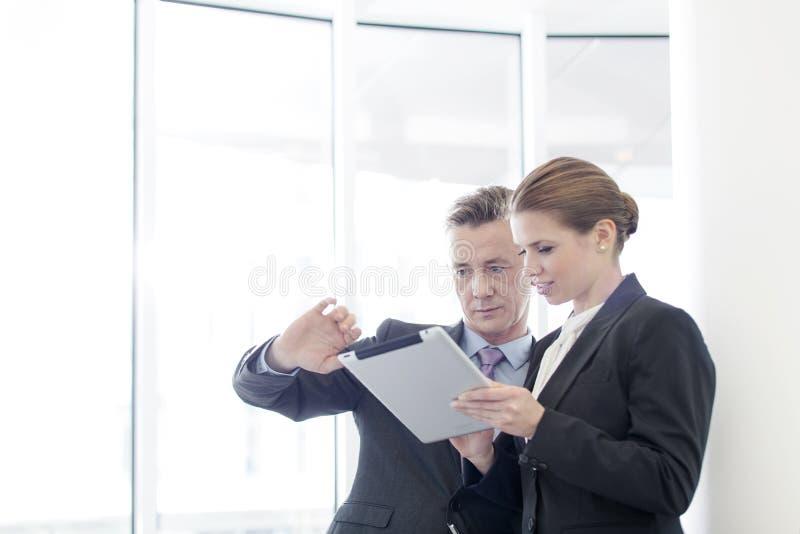 Affärsman som i regeringsställning använder minnestavlaPC med den kvinnliga kollegan royaltyfria bilder
