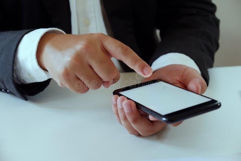 Affärsman som i regeringsställning arbetar genom att använda mobiltelefonen på skrivbordet royaltyfria foton
