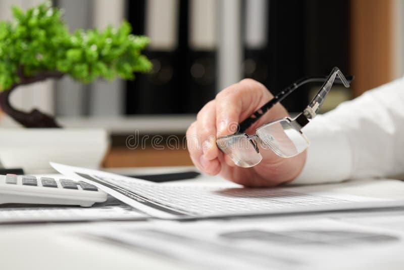 Affärsman som i regeringsställning arbetar och beräknar finans Han tar exponeringsglas begrepp för finansiell redovisning för aff royaltyfri fotografi