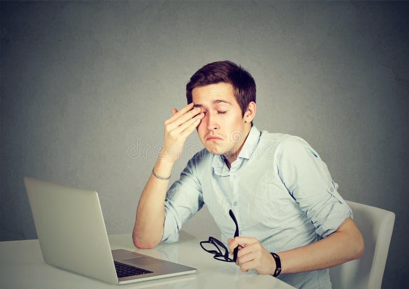 Affärsman som i regeringsställning gnider hans trötta ögon efter lång arbetstid royaltyfri bild