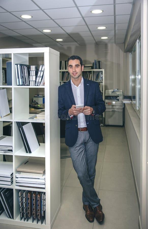 Affärsman som i regeringsställning ler och rymmer smartphonen fotografering för bildbyråer