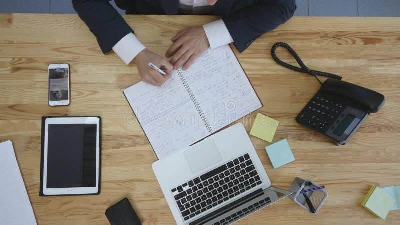 Affärsman som i regeringsställning skriver hans bråklista, manlig planläggningsdag, bästa sikt royaltyfri foto
