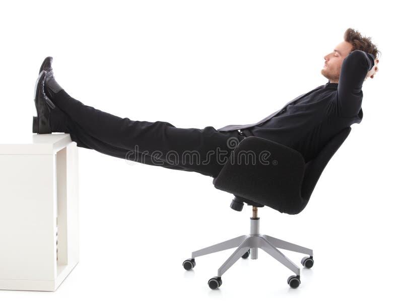 Affärsman som i regeringsställning vilar med ben på skrivbordet royaltyfri bild