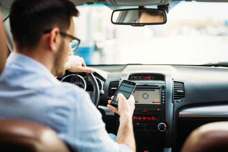 Affärsman som ignorerar säkerhet och smsar den onmobile telefonen, medan köra arkivfoto