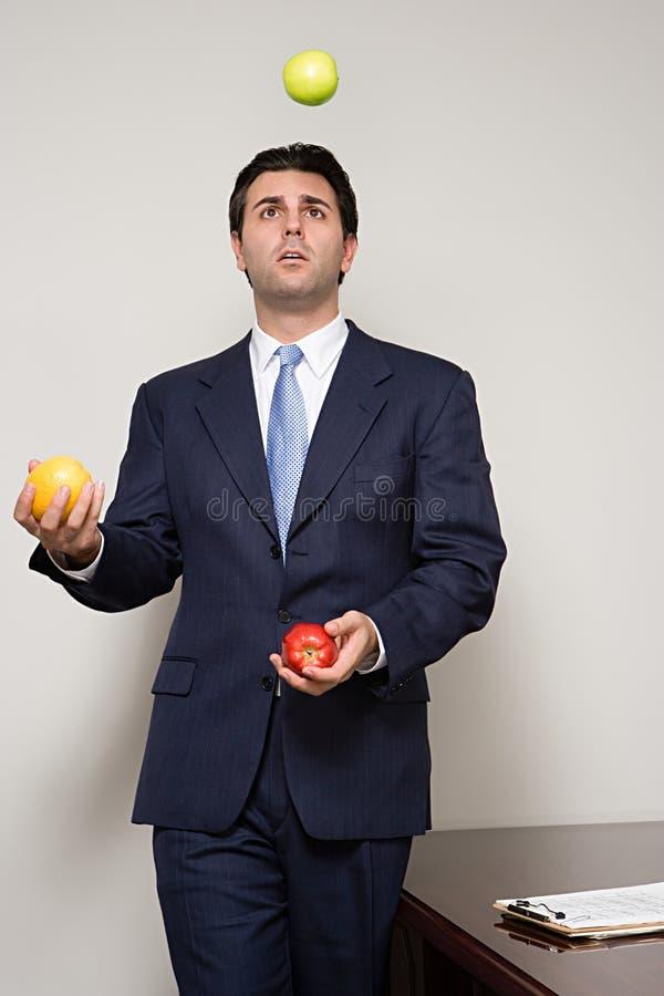 Affärsman som jonglerar frukt arkivfoton