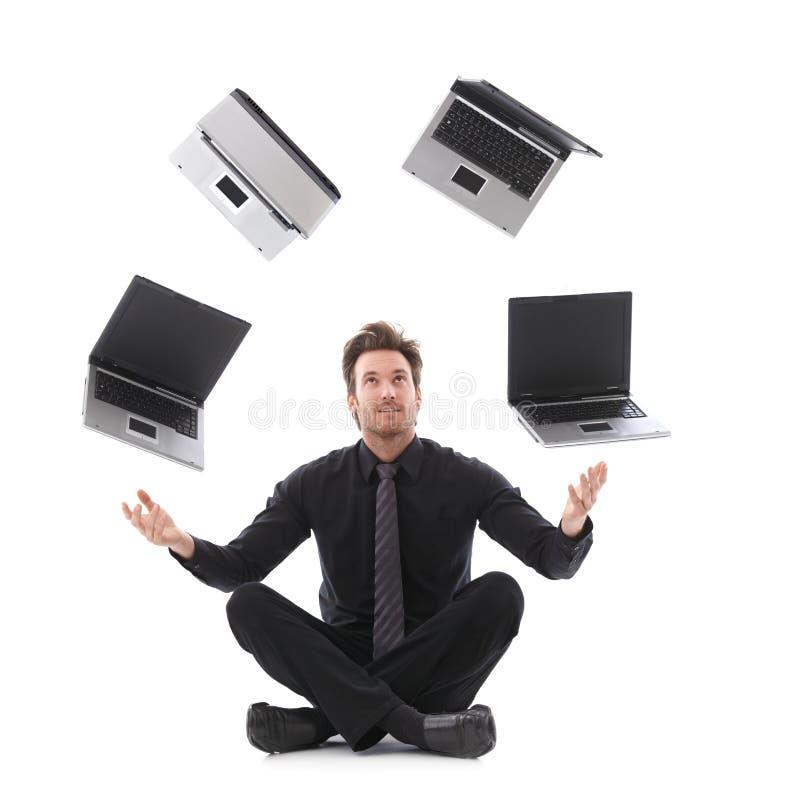 Affärsman som jonglerar med bärbar dator royaltyfria bilder