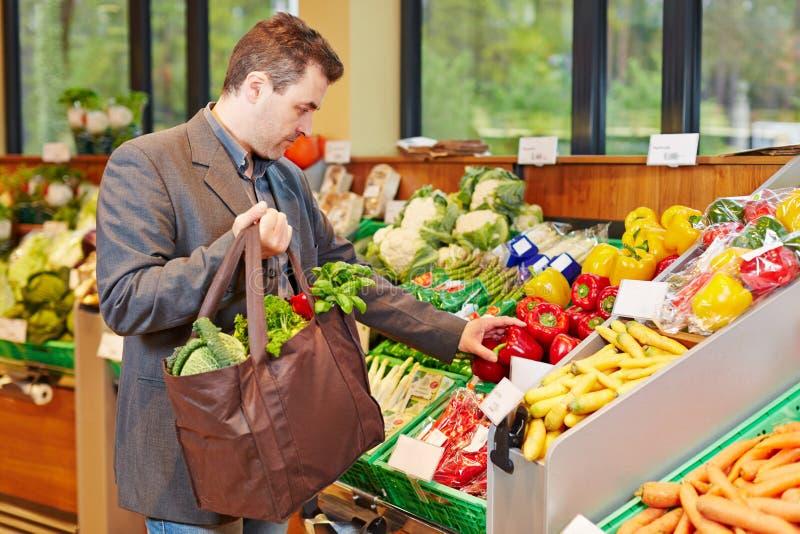 Affärsman som köper nya grönsaker royaltyfria foton