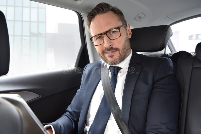 Affärsman som kör i taxi arkivbild