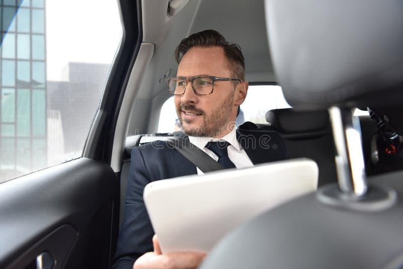 Affärsman som kör i taxi genom att använda minnestavlan arkivbilder
