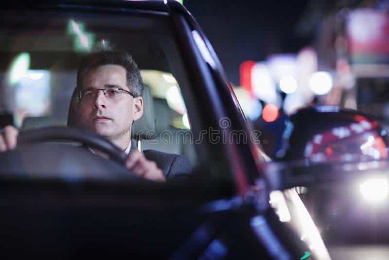 Affärsman som kör på natten i staden arkivbild