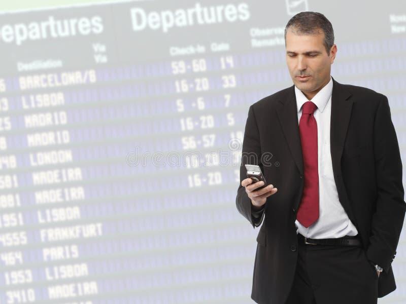 Affärsman som kallar på den mobila telefonen på flygplats royaltyfri fotografi