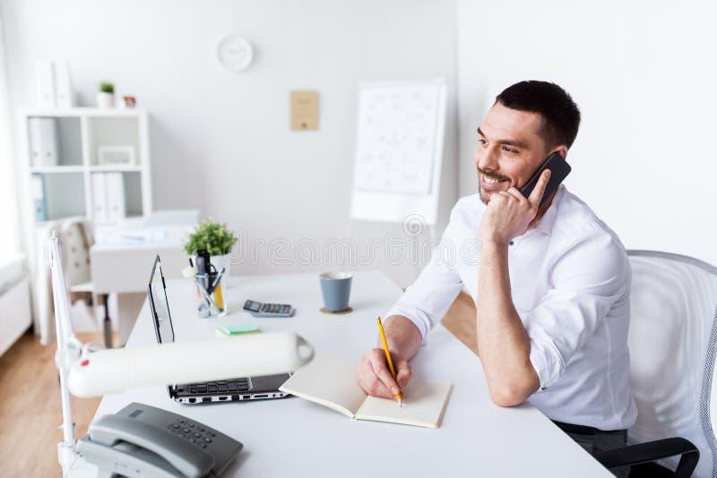 Affärsman som kallar på smartphonen på kontoret fotografering för bildbyråer