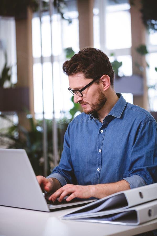 Affärsman som koncentrerar på bärbara datorn på det idérika kontoret royaltyfria foton