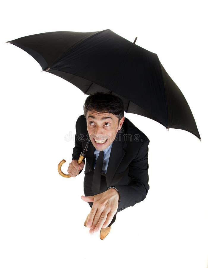 Affärsman som kontrollerar på regnet arkivfoton