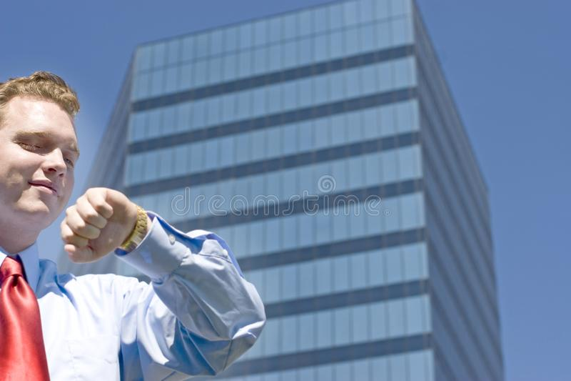 Affärsman som kontrollerar tid arkivbild