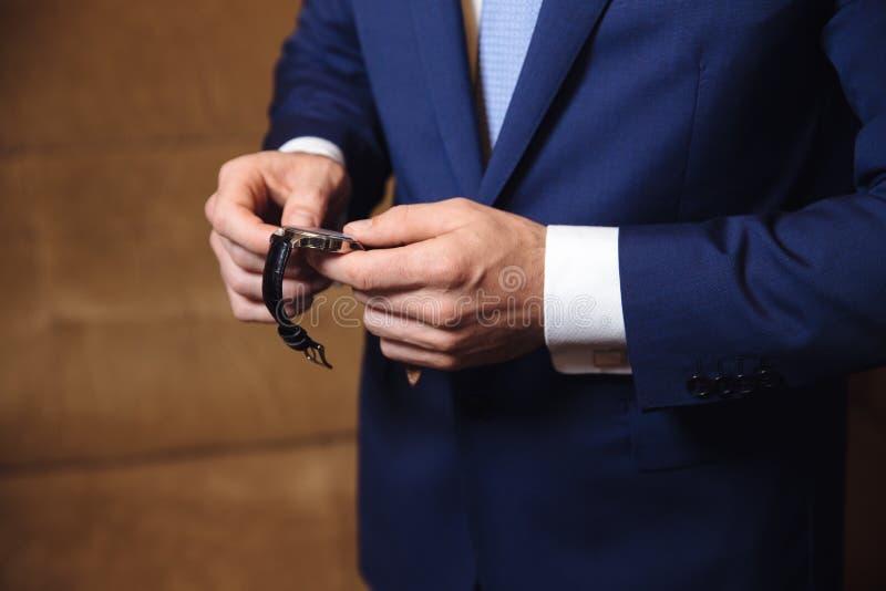 Affärsman som kontrollerar tid på hans armbandsur watch för handmän s arkivbild