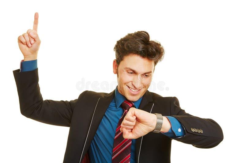 Affärsman som kontrollerar tid på hans klocka arkivfoton