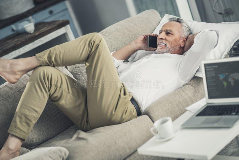 Affärsman som kopplar av, medan ligga på soffan royaltyfri foto