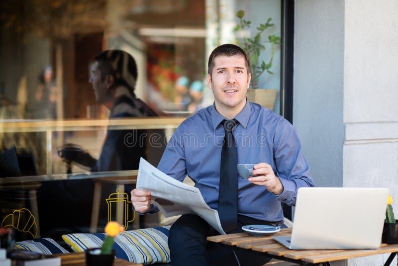 Affärsman som kopplar av på kaféterrassen i morgonen som dricker kaffe och läser den finansiella tidningen royaltyfria foton