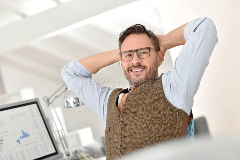 Affärsman som kopplar av på kontoret royaltyfri bild