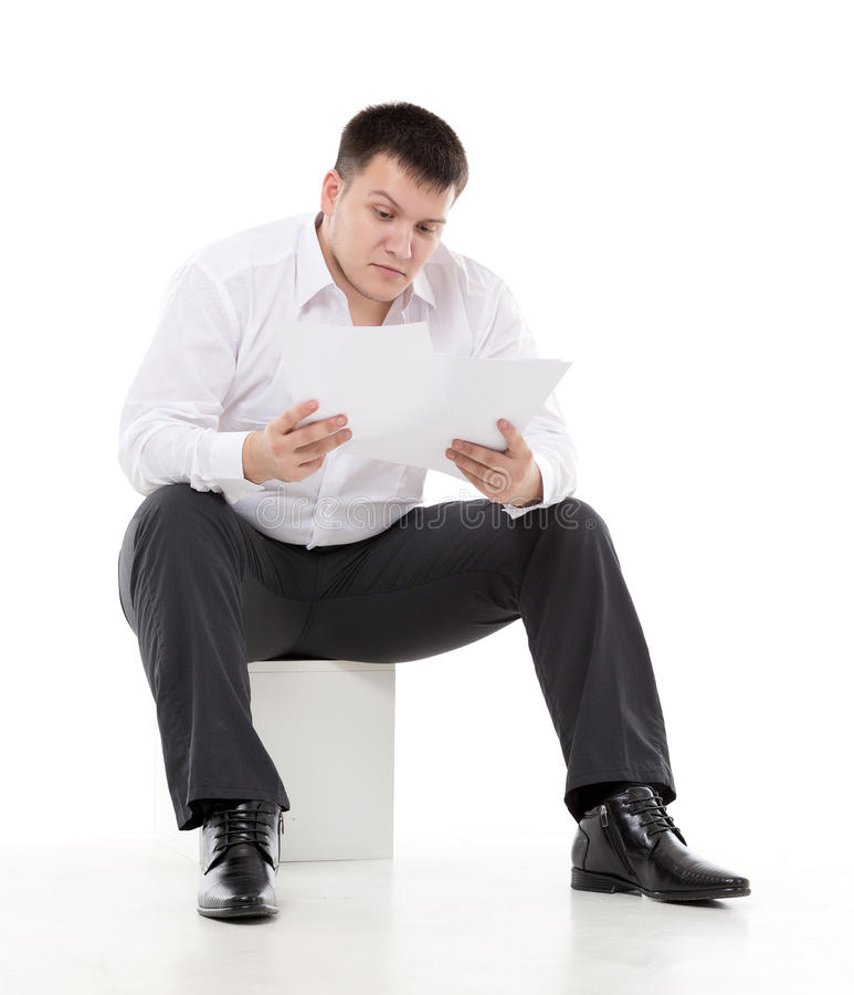 Affärsman som läser en rapport med skepsis royaltyfria foton