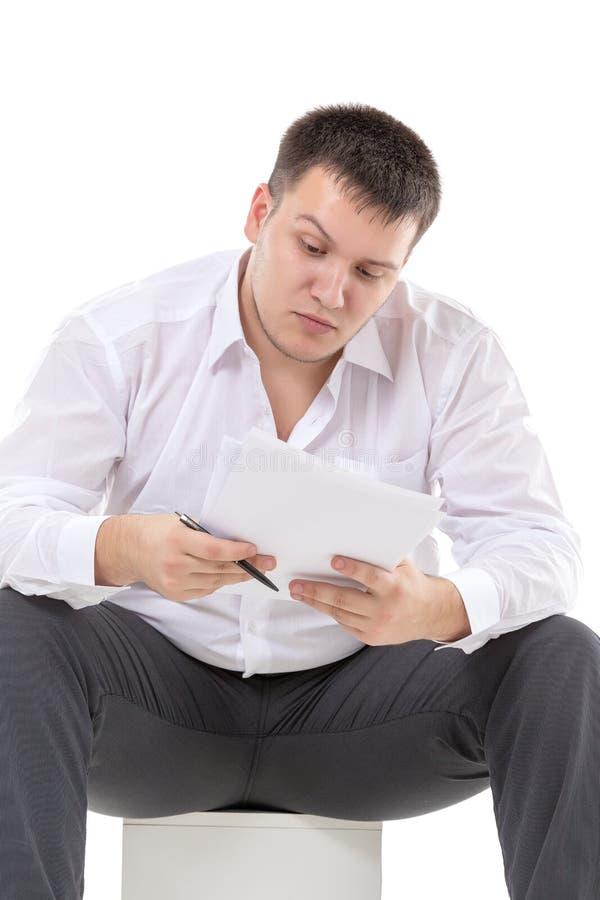 Affärsman som läser en rapport med skepsis arkivfoton