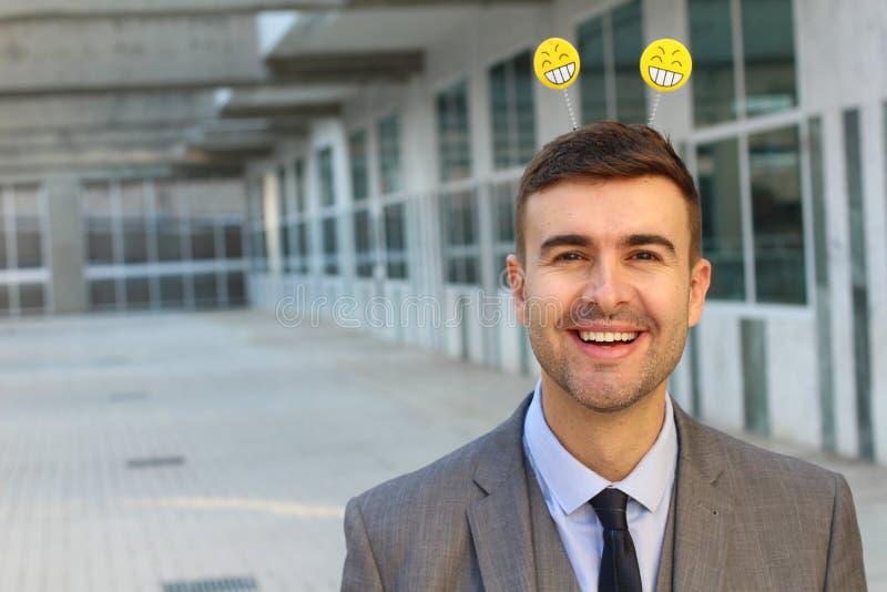 Affärsman som ler med den smiley headwearen fotografering för bildbyråer