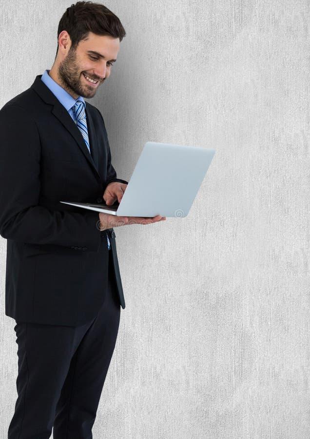 Affärsman som ler, medan genom att använda bärbara datorn mot väggen stock illustrationer
