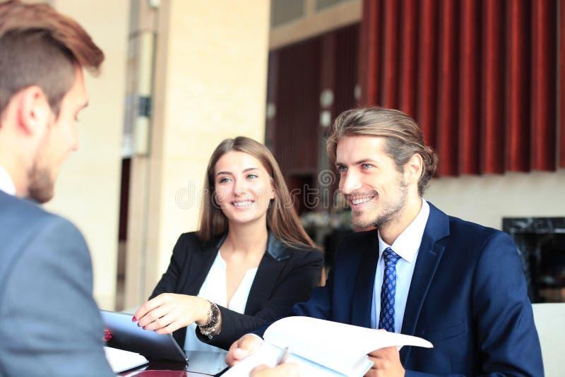 Affärsman som lyckligt ler som hans affärspartner som undertecknar slutligen det viktiga avtalet arkivfoton