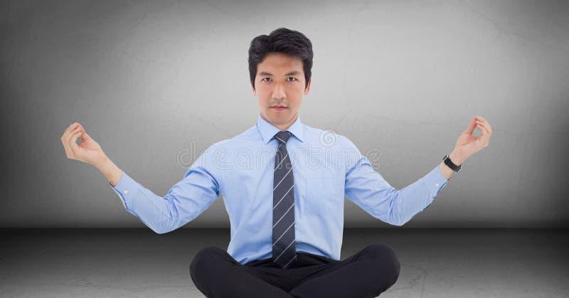 Affärsman som mediterar i grå färgrum fotografering för bildbyråer