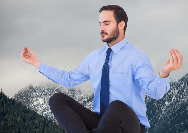 Affärsman som mediterar mot berg och grå himmel royaltyfria bilder