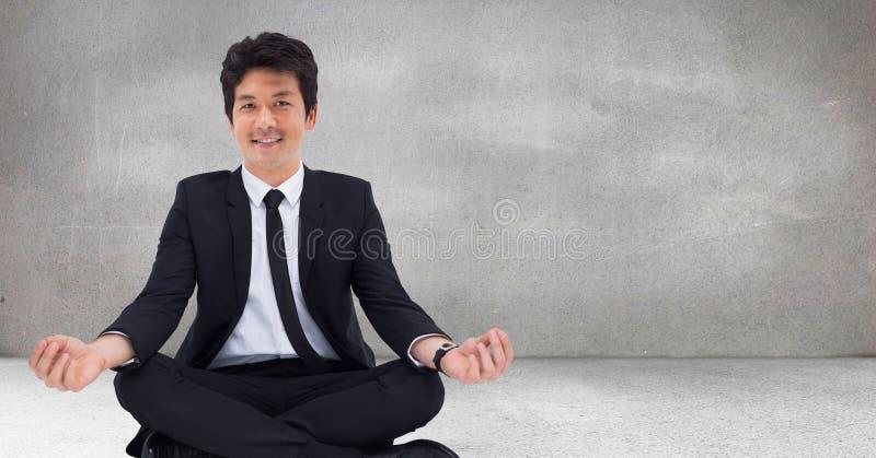 Affärsman som mediterar mot den gråa väggen royaltyfri foto