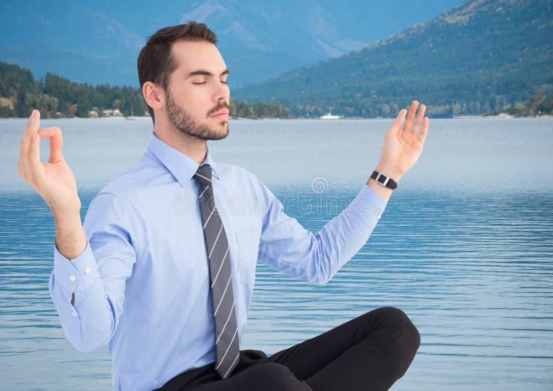 Affärsman som mediterar mot floden och kullar med träd arkivbilder