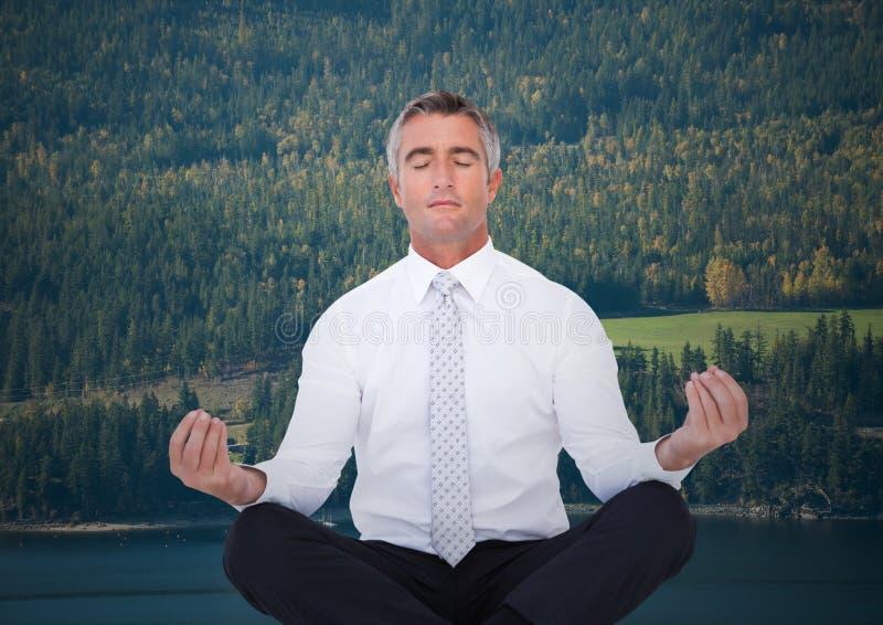 Affärsman som mediterar mot träd och floden arkivfoto