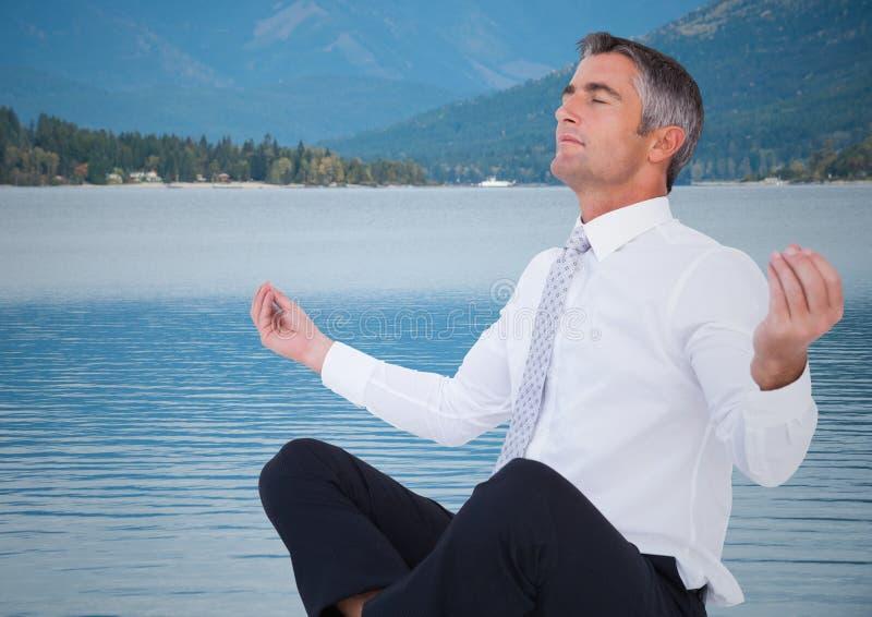 Affärsman som mediterar mot vatten och kullar royaltyfri foto