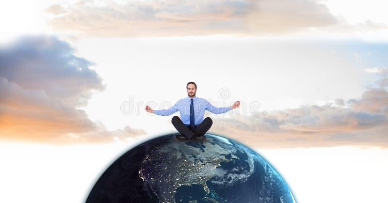 Affärsman som mediterar på jordklotet mot himmel royaltyfri bild