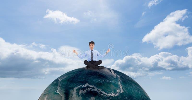 Affärsman som mediterar på jordklotet mot himmel royaltyfri fotografi