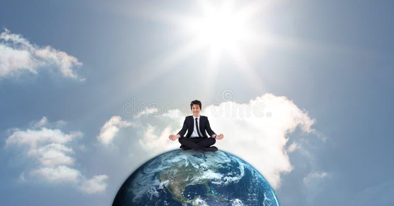 Affärsman som mediterar på jordklotet mot himmel royaltyfria bilder